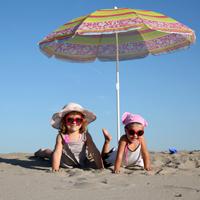 Zwei Mädchen mit Sonnenbrille und Sonnenhut liegen am Strand unter einem Sonnenschirm.