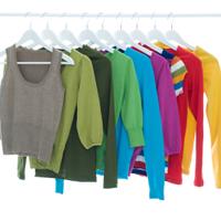 Verschiedenen Kleidungsstücke hängen farblich sortiert auf weißen Kleiderbügeln.