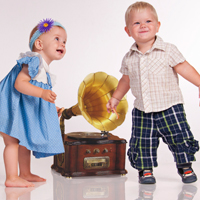 Zwei Kleinkinder bewegen sich zur Musik aus einem alten Grammophon, welches auf dem Boden steht.