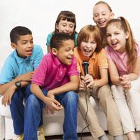 Sechs Kinder sitzen auf einem Sofa um ein Handmikrofon herum und singen.
