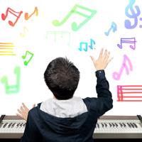 """Ein Junge sitzt mit dem Rücken zum Fotograf an einem Keyboard und """"zaubert"""" mit der rechten Hand scheinbar bunte Noten in den Raum."""