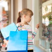 Ein Mädchen steht vor einem Schaufenster und zeigt auf ein Produkt, obwohl es schon mehrere Einkaufstüten trägt.